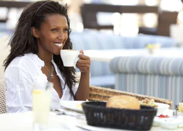 Happy woman eating breakfast, holding cup of coffee in left hand.
