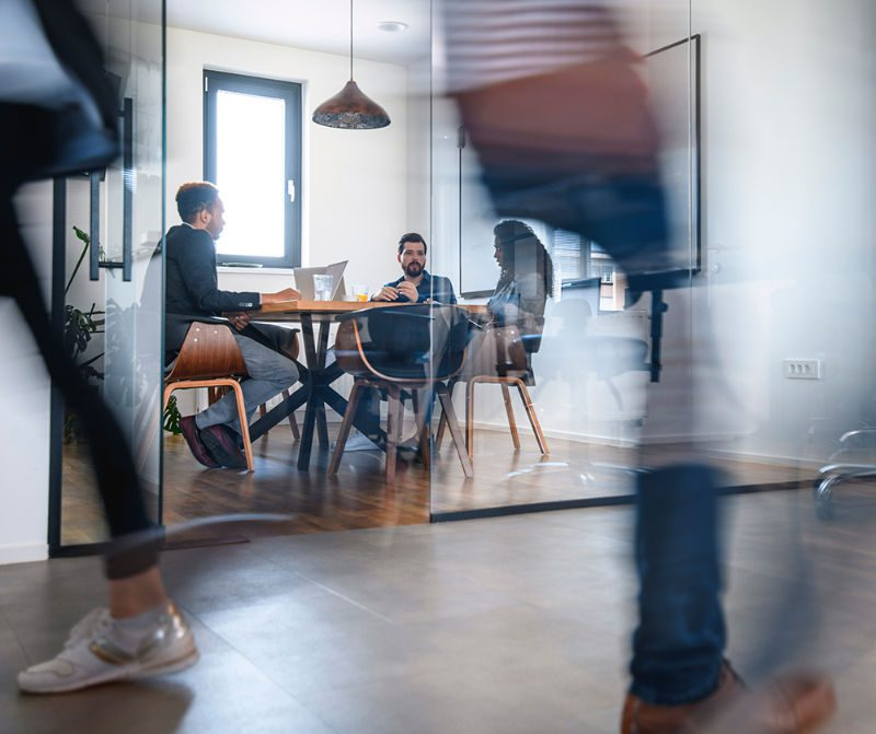 Workspace with table and three people having a discussion